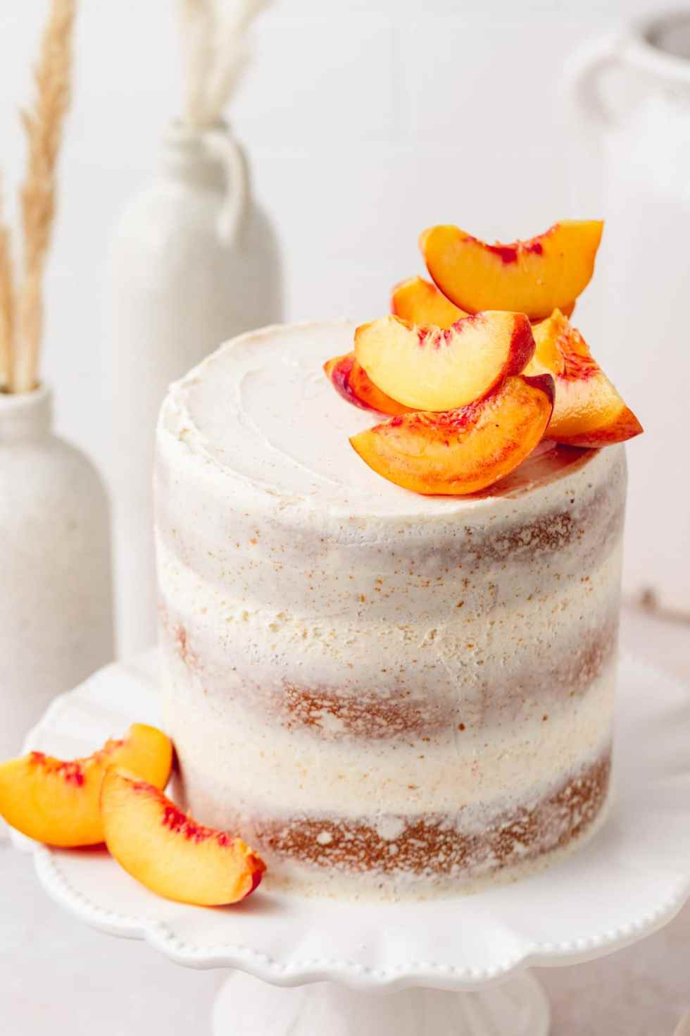 close up of brown butter peach layer cake with fresh peaches on top