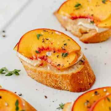 close up shot of peach and brie crostini