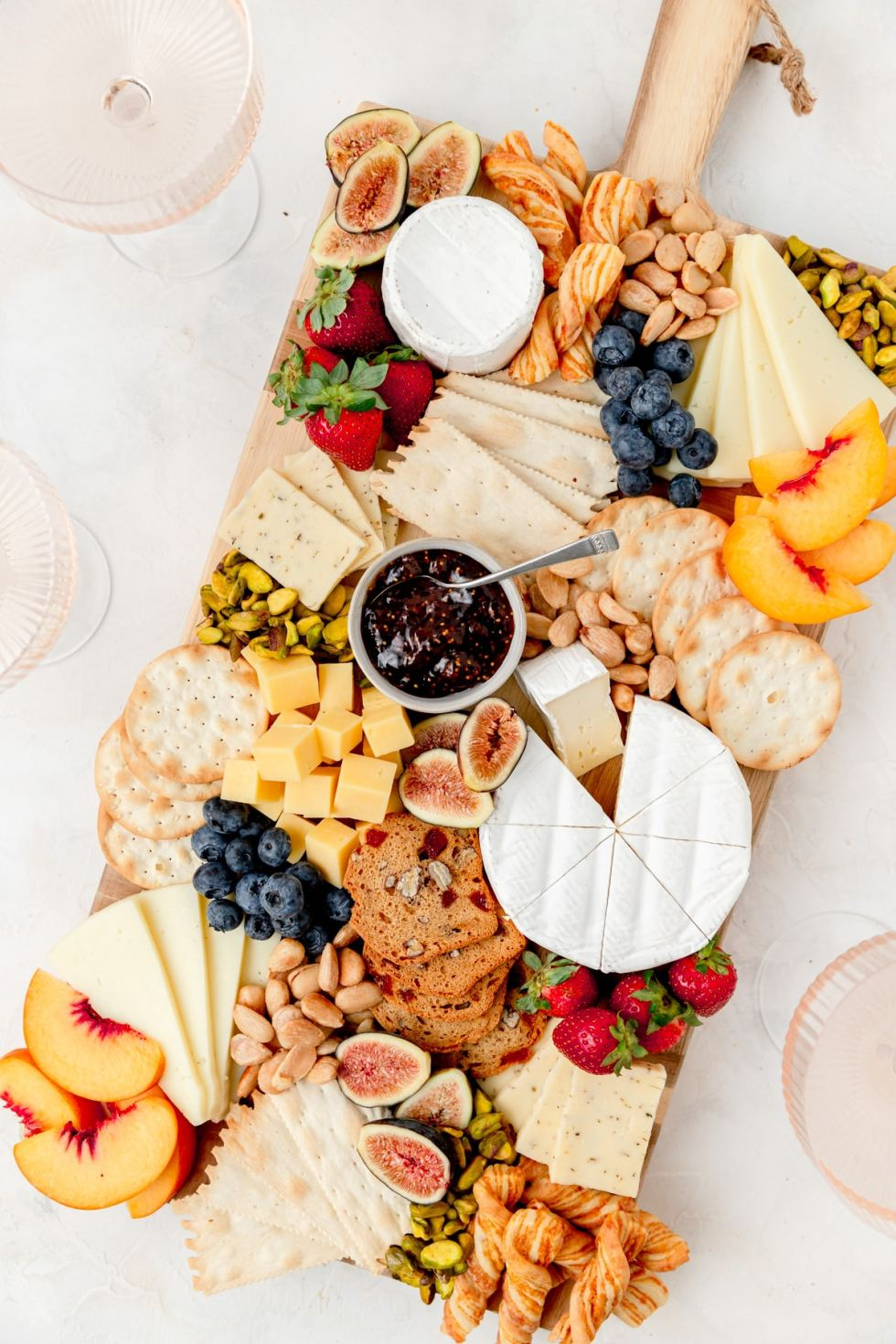 summer cheeseboard with lots of fruit and nuts on board