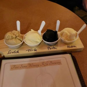 """four single-serving cups of ice cream on a """"beer flight"""" board"""