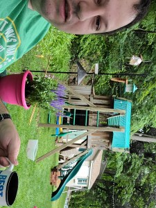 Ceetar drinking coffee out of a blue and white 'Best Dad Ever' mug in front of a swingset and a bird feeder