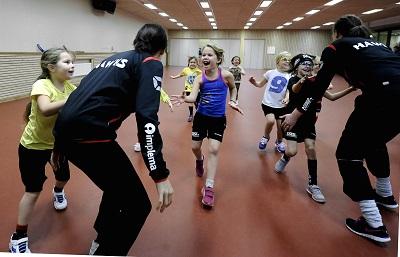 Barn och ledare i en sporthall
