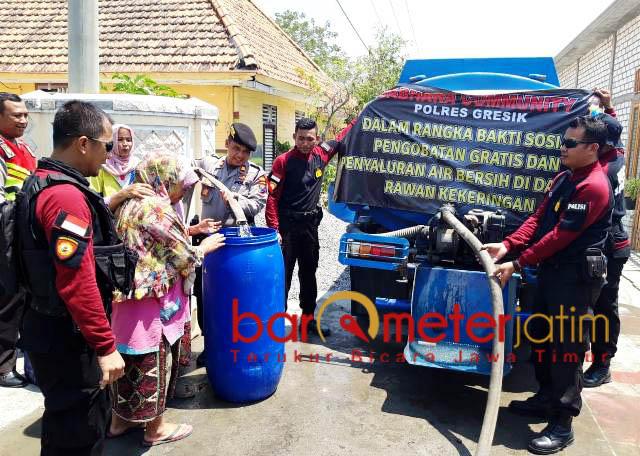 BANTUAN AIR BERSIH: Polres Gresik memberikan bantuan air bersih di Desa Keramat dan Tumapel, Duduk Sampeyan, Sabtu (29/9). | Foto: Barometerjatim.com/DIDIK HENDRIYONO