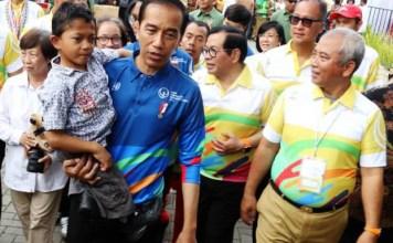 DALAM GENDONGAN PRESIDEN: Presiden Jokowi menggendong Mukhlis Abdul Holik, bocah penyandang disabilitas saat peringatan HDI di Bekasi, Senin (3/12). | Foto: IST