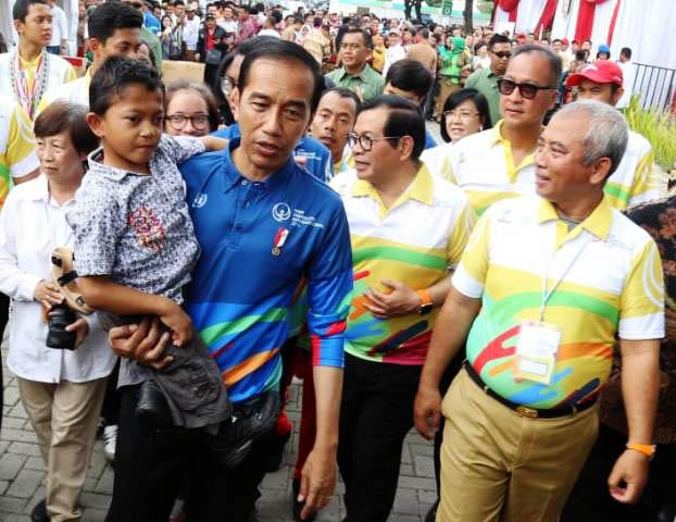 DALAM GENDONGAN PRESIDEN: Presiden Jokowi menggendong Mukhlis Abdul Holik, bocah penyandang disabilitas saat peringatan HDI di Bekasi, Senin (3/12).   Foto: IST