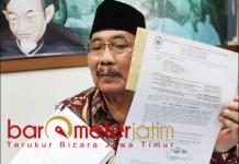 SIAP MELAWAN: Cak Anam menunjukkan surat perintah untuk eksekusi Astranawa. | Foto: Barometerjatim.com/ROY HS