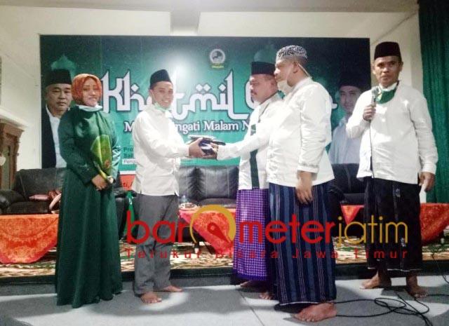 BERBAGI: Putra Kiai Asep, Muhammad Al Barra alias Gus Bara (dua kiri) bagikan sarung. | Foto: Barometerjatim.com/IST