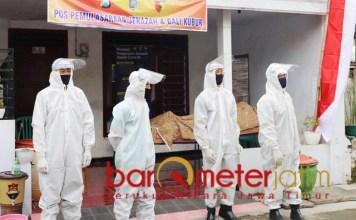 SIAGA: Petugas lengkap dengan baju hazmat di depan rumah pemulasaraan jenazah.   Foto: Barometerjatim.com/ROY HS