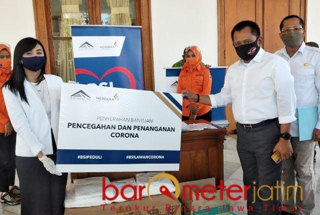 BANTUAN PT BSI: Heru Tjahjono menerima bantuan dari PT BSI di Gedung Negara Grahadi, Surabaya. | Foto: Barometerjatim.com/ROY HS