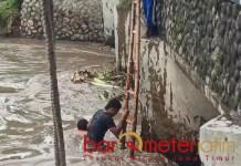SAMPAH KAYU: Dua orang warga membersihkan sampah kayu di Bendungan Rolak 70, Sabtu (6/2/2021). | Foto: Barometerjatim.com/ROY HS