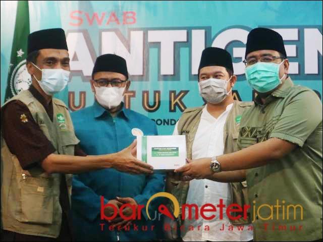 SWAB ANTIGEN: Anwar Sadad (kanan) menyerahkan swab antigen ke Ketua PCNU Surabaya, KH Muhibbin Zuhri.   Foto: Barometerjatim.com/RETNA