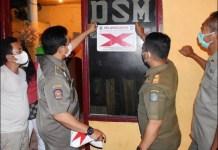 MELANGGAR: Petugas menandai tempat usaha di Surabaya yang melanggar protokol kesehatan. | Foto: Barometerjatim.com/IST
