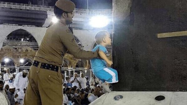 صورة | موجة إعجاب برجل أمن سعودي رفع طفلاً لتقبيل  الكعبة !