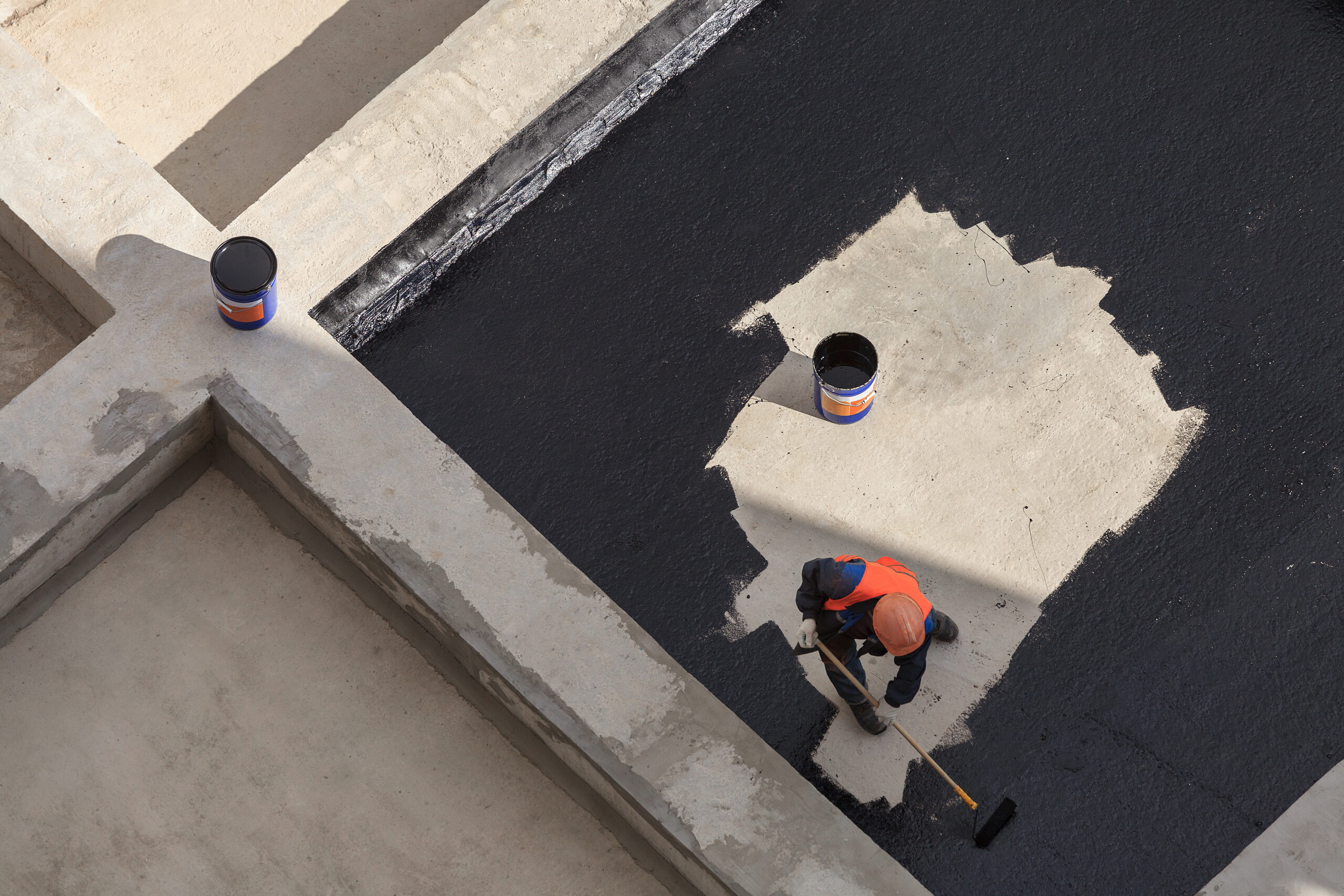 The worker in overalls applies an insulation coating on the concrete surface. View from above.