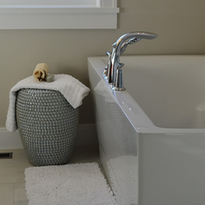 A bathtub with centre taps and linen basket next to ma