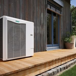 Air source heat pump installation on the side of a home