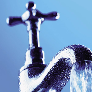 A running tap close up with a blue background