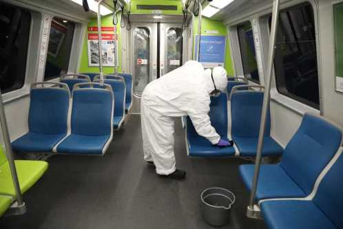 A BART employee cleaning a train car seat