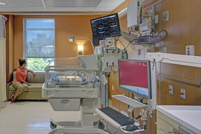 Woman looking out window in NICU patient room with medical equipment