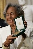 Rachel Robinson is shown accepting the Congressional Medal of Honor for her husband in 2005. (Photo credit: Eric Draper, Wikimedia Commons)