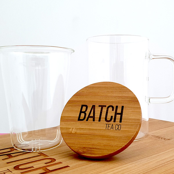 Glass mug with infuser basket sitting separately showing branded bamboo lid