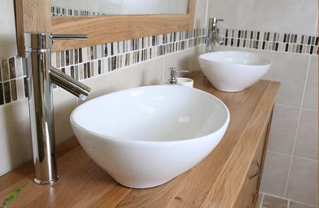 Close-Up Side View of Two White Ceramic Oval Basins on Large Oak Topped Vanity Unit