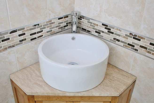 Closeup of Round Ceramic Basin on Travertine Top Vanity Unit in a Corner