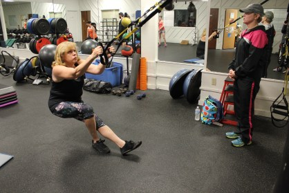 Pictured to the left is Bonnie Weissman using the TRX Suspension training system and to the right is trainer Gina Stonich.