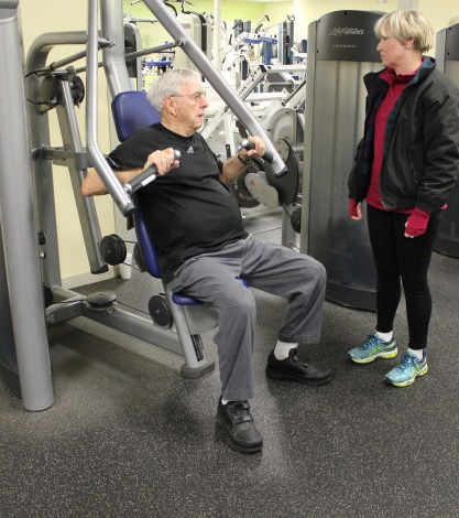 Perry, left, works out on the chest press machine while Gina oversees his fitness routine.