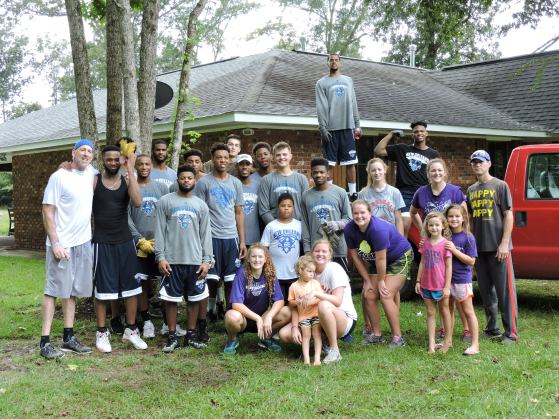 The UNO men's basketball team and Hughes's family in front of their flood ravaged home.