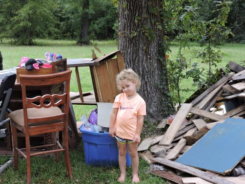 Hughes's youngest sister, Harlie, standing by the ruined contents of their home.