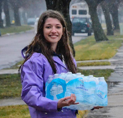 Asha is carrying water bottles to houses in Flint.