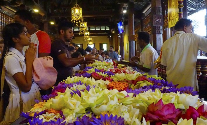 Worshippers bringing flowers to the Temple of the Sacred Tooth Relic