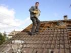 Dachdecker beim Abdecken von alten Dachzieglen