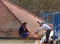 Dachdecker sitzt auf Dachrinne