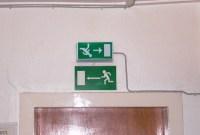 Schilder für Fluchtwege zeigen in zwei Richtungen