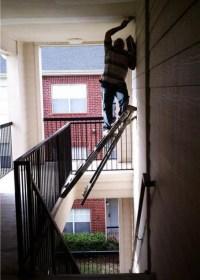 Maurer steht auf einer Leiter die über eine Treppe gelehnt ist