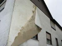Außenputz einer Fassade löst sich wie Tapete ab
