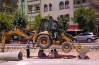 Straßenarbeiter halten Mittagspause unter einem aufgebockten Radlader