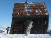 Mann drückt gegen ein schiefes Haus Hütte aus Holz