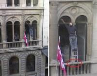 Fensterputzer steht mit Stehleiter auf Balkonsims