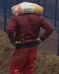Bauarbeiter trägt Zementsack auf Schultern ohne Hände