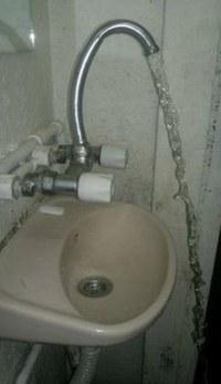 Wasser aus Hahn läuft über Waschbecken