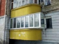 Eckiger Wintergarten aus Glas zwischen gelben runden Balkonen