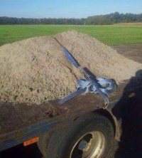 Sand auf Ladefläche von Lastwagen mit Spanngurt gesichert