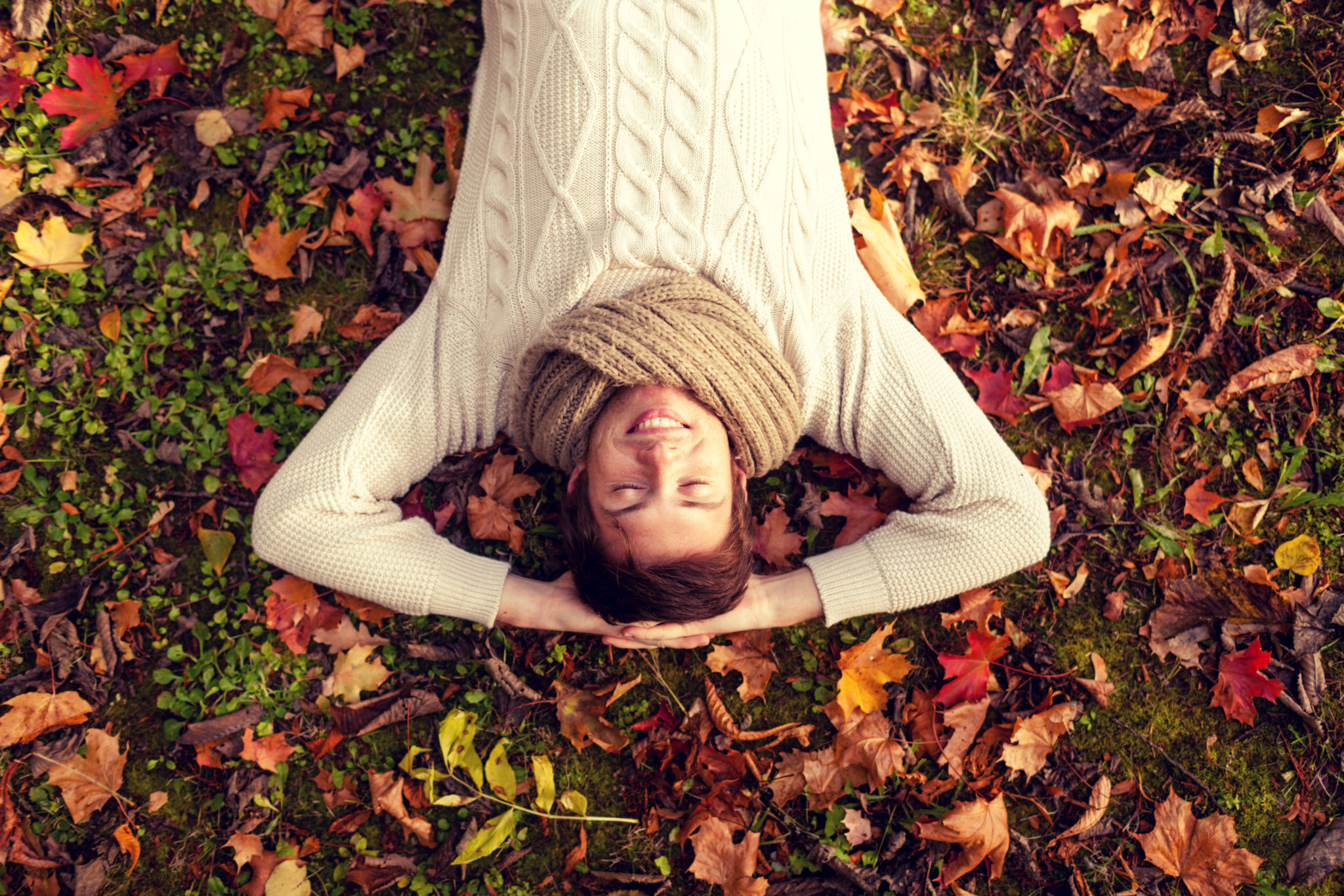 Man in scarf and sweater, lying in the fall leaves