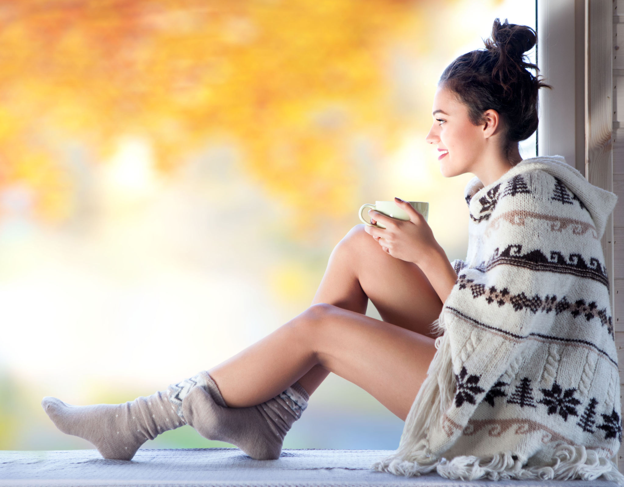Woman in winter sweater and socks with a hot drink