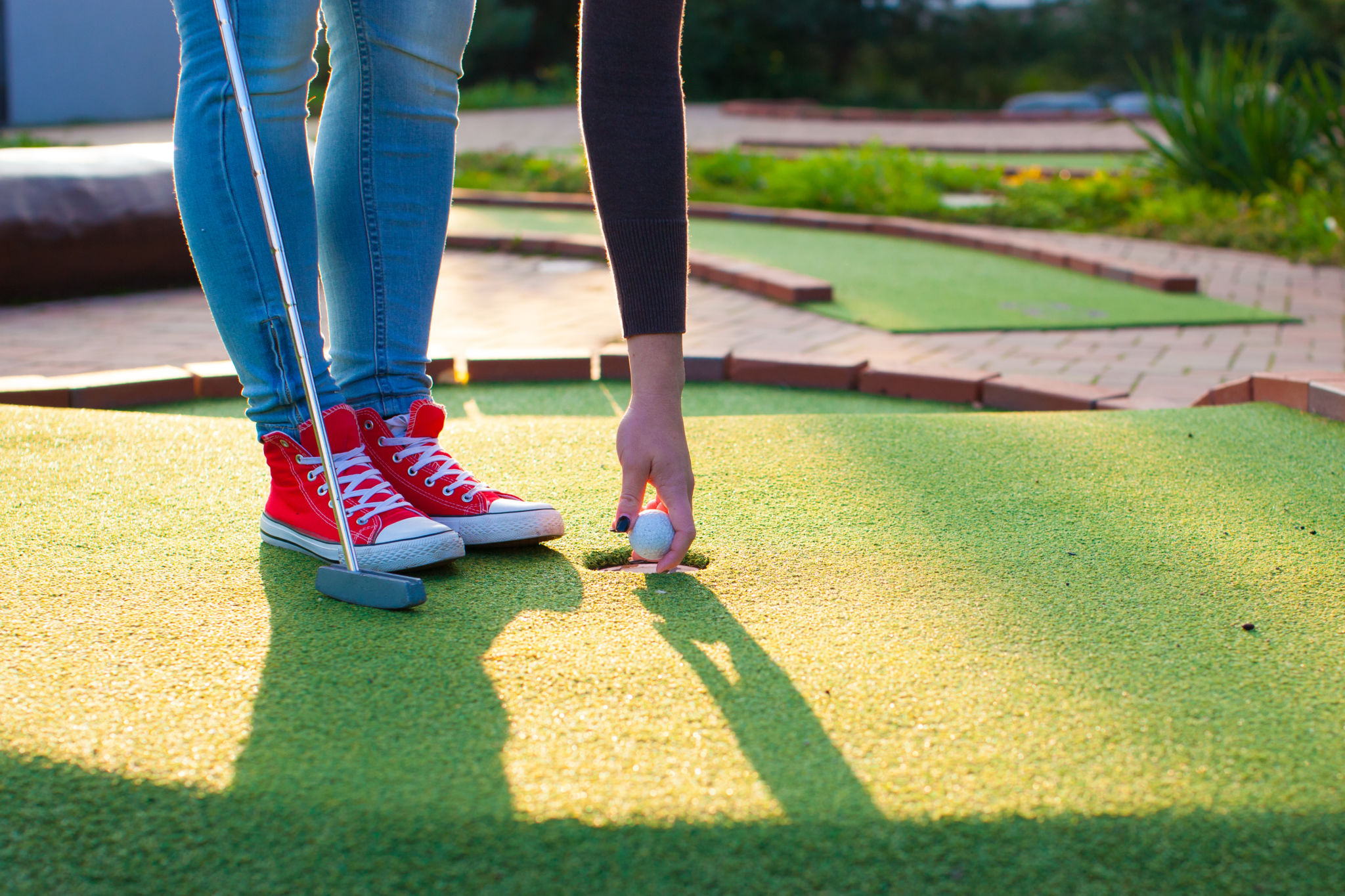 woman's arm and legs as she picks up a golf ball at bay area mini golf