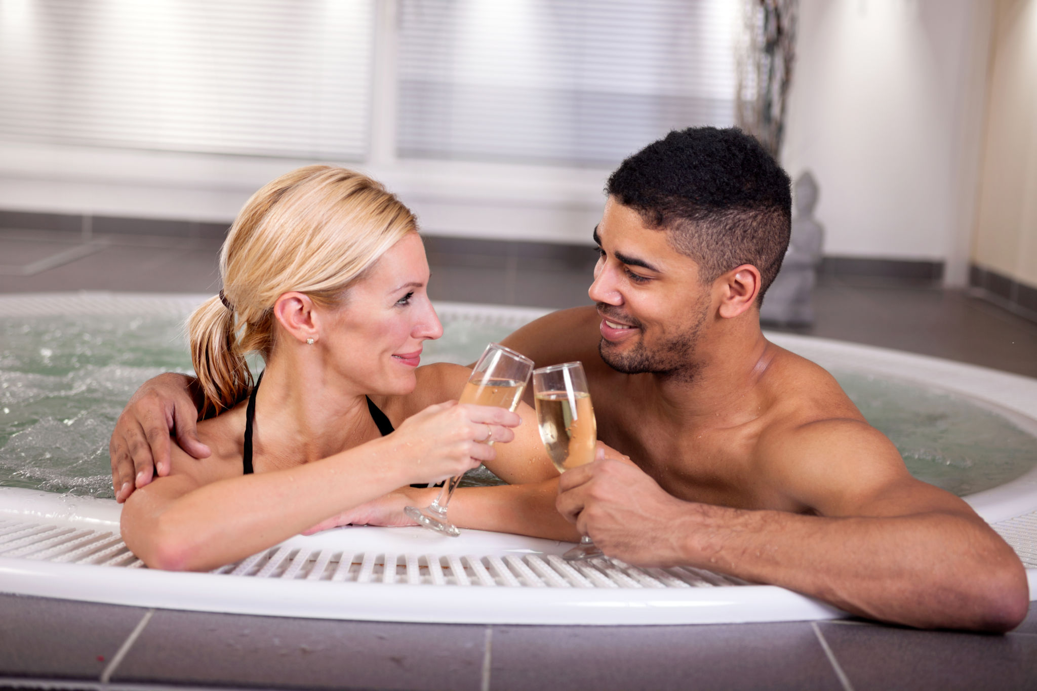 couple toasting each other with champagne in a hot tub