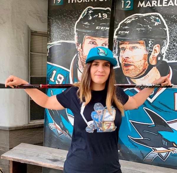 Female model wearing Hertl t-shirt with hockey stick